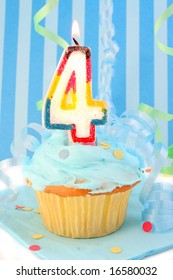 boy's fourth birthday cupcake with blue frosting and  decorative background