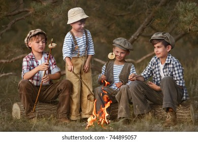 Boys fry sausages and bread in the woods at the stake on a summer evening