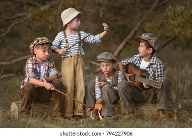 Boys fry sausages in the woods at the stake on a summer evening