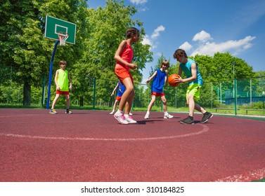 Boys and girl play basketball game on playground