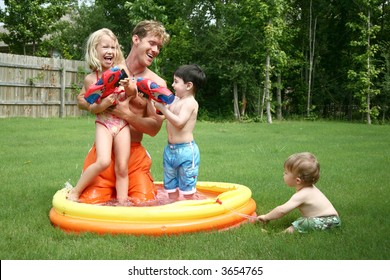 Boys and girl play with dad in the kiddie pool with water guns