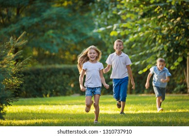 Boys and girl play and run a race on the lawn outdoor