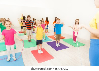 Boys and girls jumping with skipping rope in gym