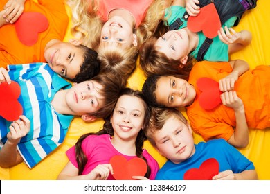 Boys and girls laying on the floor in circle with hearts in their hands