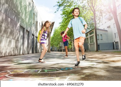 Boys and girls play hopscotch in the school yard