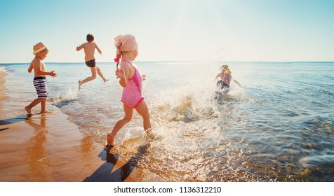 Boys and girls playing on the beach on summer holidays. Children in nature with beautiful sea, sand and blue sky. Happy kids on vacations at seaside running in the water