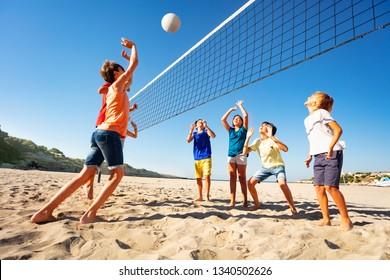 Jungen und Mädchen spielen Volleyball am Strand