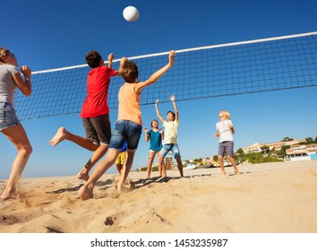 Boys and girls playing volleyball on the beach