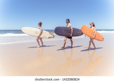 Boys and girls teen surfers with surfboards walking at a sandy beach.