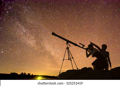 Boys and girls telescopic. Milky Way galaxy, rice paddy fields and mountains. Long exposure photograph, with grain.Image contain certain grain or noise and soft focus.