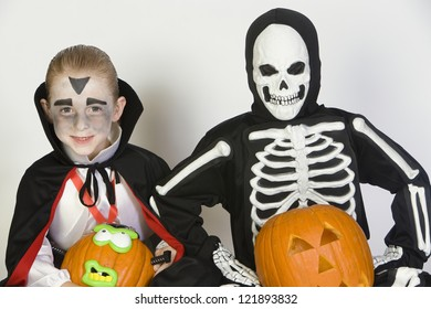 Boys in Halloween outfit together with pumpkins isolated over white background