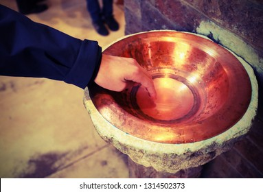 boy's hand dip in the blessed stoup water in church and vintage old effect
