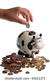 A boy's hand dropping a coin into a piggy bank