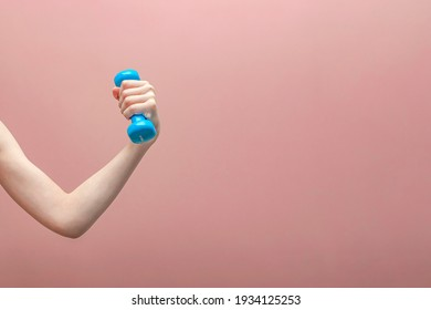 Boy's hand holding a dumbbell on a pink background.Sports concept. Banner ,postcard and panoramic edition. copy space text
