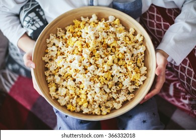 boy's hand holding a large bowl of popcorn
