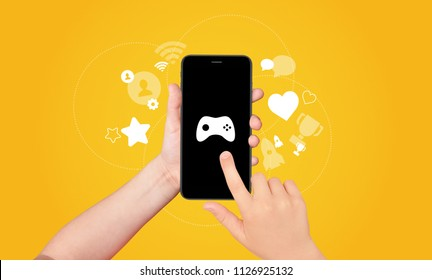 Boy's hand holding and touching the screen of smartphone with game joystick on screen with award and achievement icons on yellow background. Gamification concept