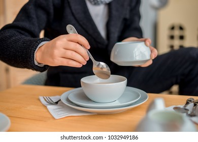 the boy's hand pours sugar into a white cup of tea