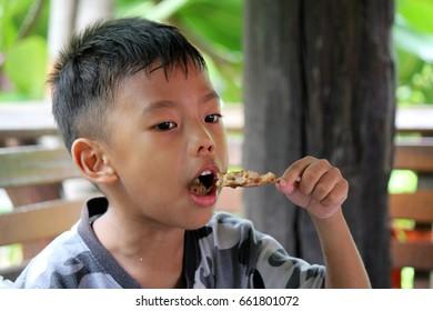 Boys are happy to eat pork skewers.