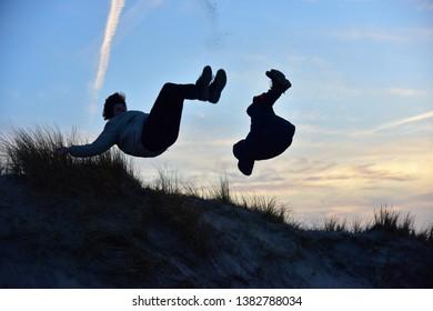 Boys having fun with free backflips in the dunes, North Sea beach, Jutland/Denmark