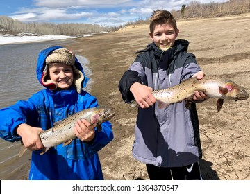 Boys holding fish they caught in a lake in late winter