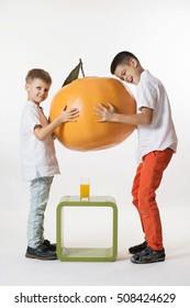 Boys are with huge tangerine any orange juice