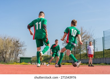 Boys kicking football on the sports field