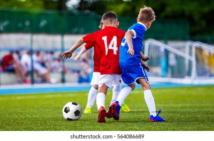 Boys Kicking Soccer Ball on Grass Pitch. Children Football Players Playing Match on the Stadium. Soccer Game for Kids