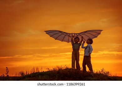 Boys launch a kite in the field at sunset