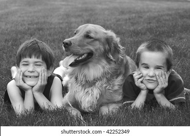 Boys Laying in the grass with Dog