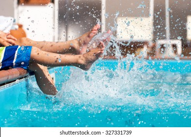 Boys legs splashing water in pool, summer holiday