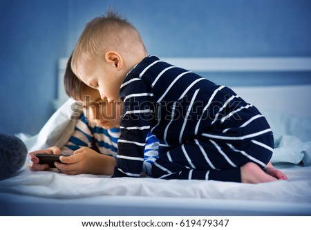 boys lying in bed and playing in smart phone. childrens watching movie at night