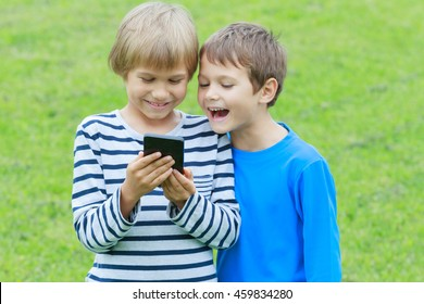 Boys with mobile phone. Children smiling, looking to screen, playing games or using application. Outdoor. Technology education leisure people concept