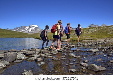 Boys in mountain walk, are fording a stream in the Nivolet pass on the Gran Paradiso National Park.
