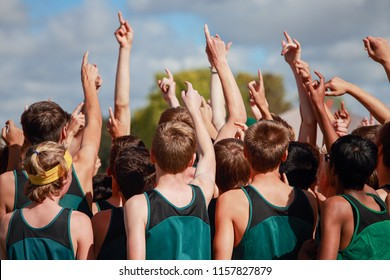 Boys on cross country team in a huddle raising arms pointing their fingers showing number one