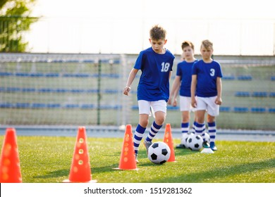 Boys on Sports Training. Football Training Dribbling Cone Drill. Young Boys of School Junior Soccer Team Practicing on Grass Field. Kids Improving Football Skills