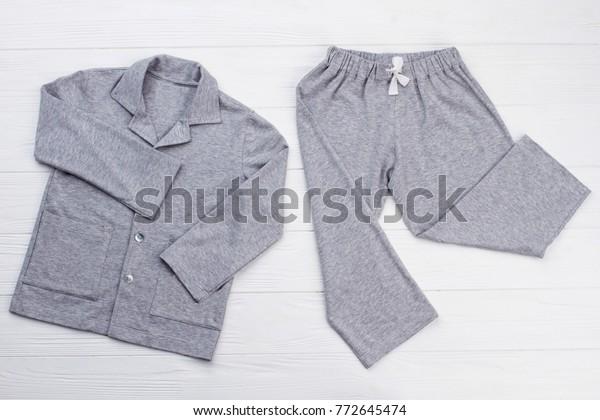 白い背景に少年のパジャマ。柔らかい灰色のまん延綿。ゆったりしたシャツとパンツで夜の安眠を実現。