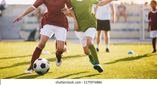 Boys Play Football. Running Football Soccer Players. Kids at Soccer Field Running with Ball. An Action Sport Picture of a Group of Children Playing Soccer Football Game