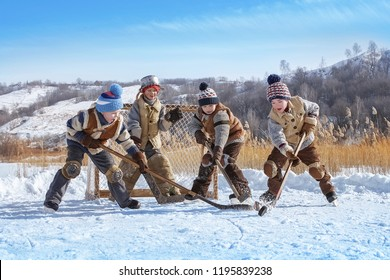 Boys play hockey on a frozen lake on a winter sunny day