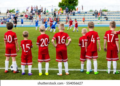 Boys Play Soccer Match. Children Sport Team. Youth Sports Team Together. Football Soccer Game For Children. Kids Soccer Players on bench Watching Tournament Game with Coach. Stadium in the Background