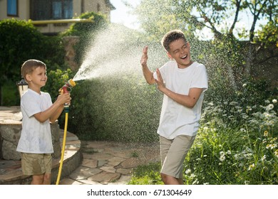 Boys play with water sprinkler at sunny summer day