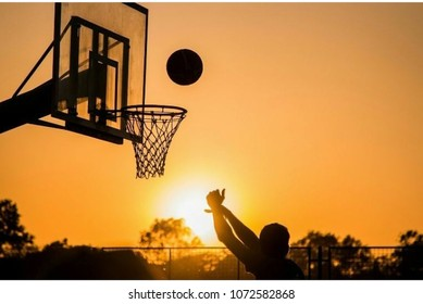 boys playing basketball in sunset