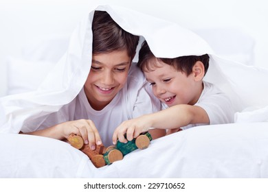 Boys playing in bed with wooden toys - brothers enjoying time together