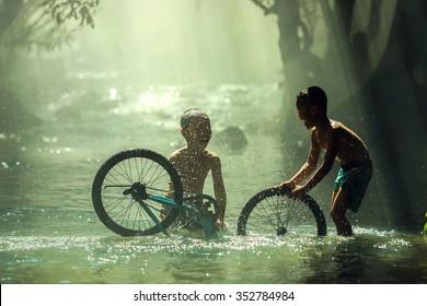 The boys playing with bicycle water splash on creek,Nhongkhai,Thailand.