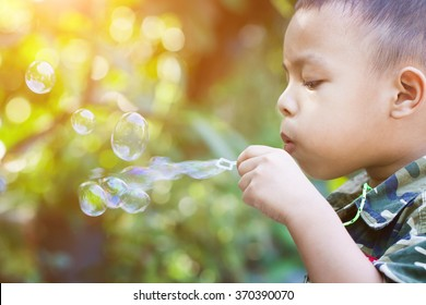 The boys are playing blowing bubbles