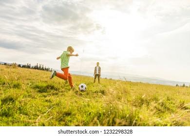 Boys playing football in a meadow, having fun