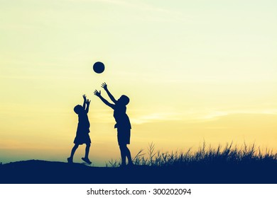 boys playing football at sunset. silhouette concept