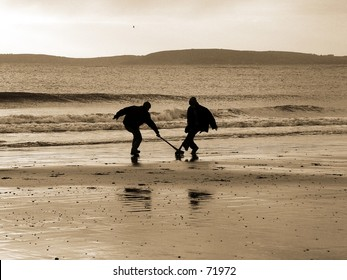 Boys playing the Irish game hurling on a beach by the sea