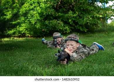 Boys playing in lasertag shooting game, boy with a gun, war simulation.