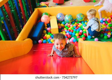 Boys playing on the playground, in the children's maze with balls. Multi-colored balls.