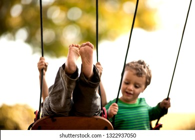 Boys playing on a swingset.